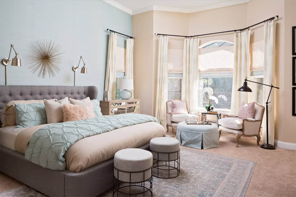 Charming light blue and yellow master bedroom features a gray tufted bed with a pair of stools on its edge that sits on a vintage rug over a carpet flooring.