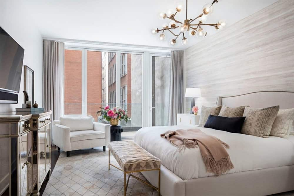 A huge catalyst modern chandelier illuminated this white elegant master bedroom. It features a beautiful wood wallpaper on the bed area, a white accent chair that matches the bed and a floor to ceiling windows that brightens the room.