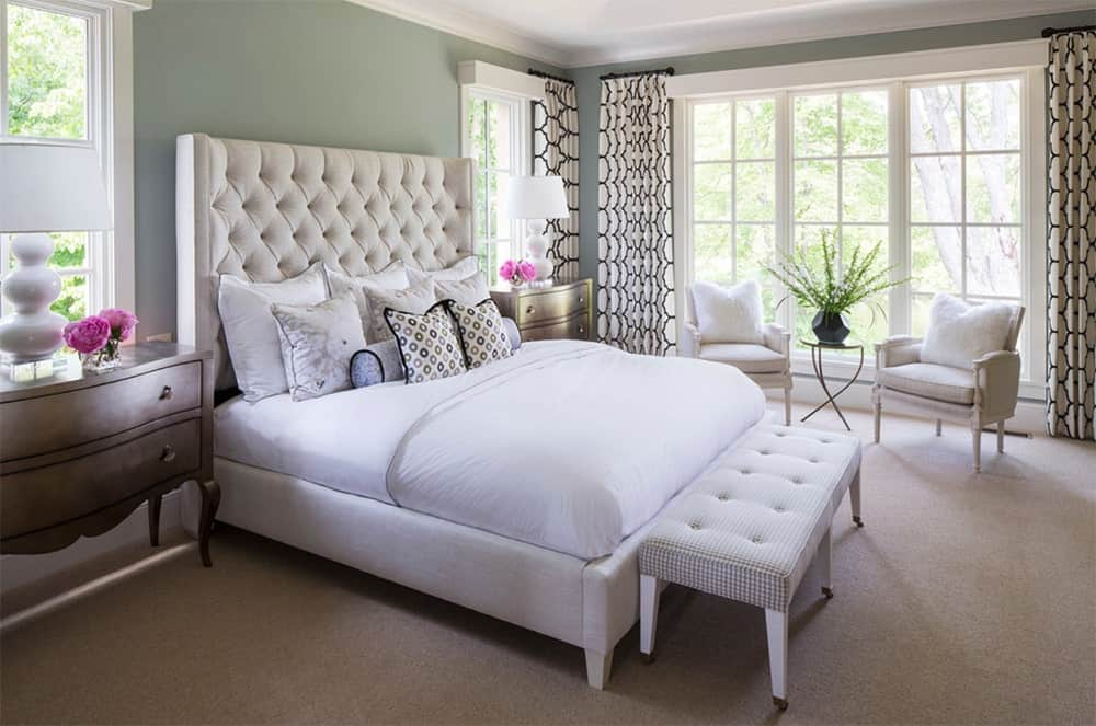 Transitional master bedroom with lovely white table lamps that complements the tufted bed, bench and armchairs. It also has carpet flooring and glass framed windows with white patterned curtains.