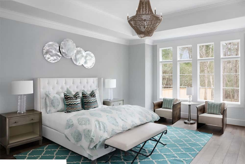 Gorgeous master bedroom with a white bed that complements the gray wall and is accented by a tiffany blue patterned rug over a hardwood flooring.