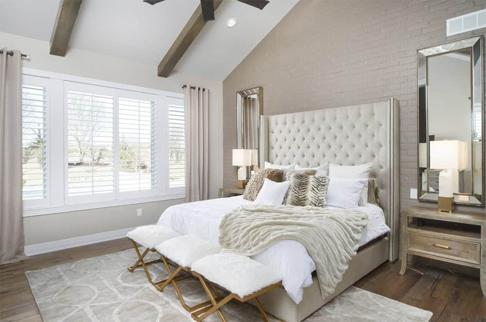 Fabulous master bedroom features hardwood flooring, brick accent wall and a vaulted ceiling with exposed wood beams.