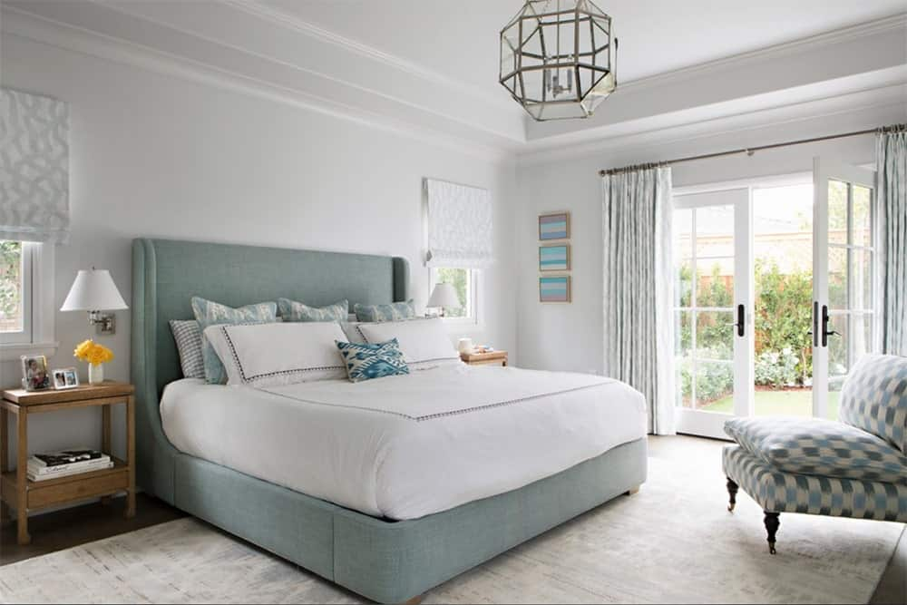 Calming master bedroom with white walls, hardwood flooring and a modern geometric chandelier that hung over the bed.