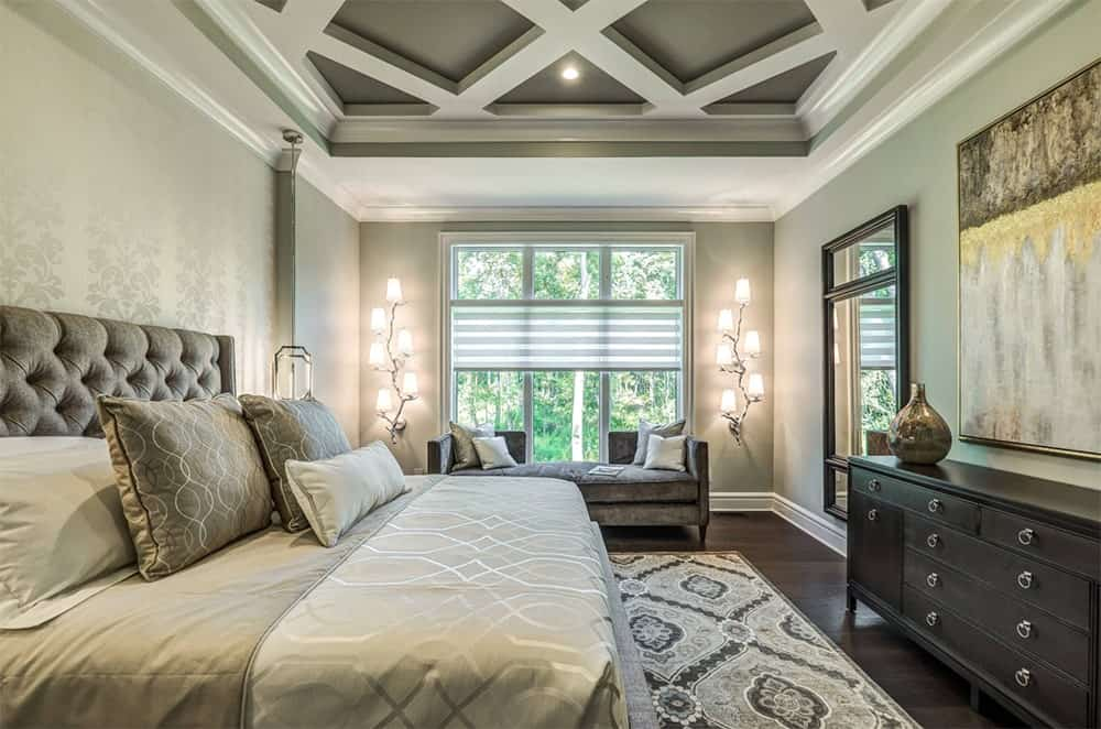 Cozy master bedroom features a coffered ceiling, a large bed over a beautiful patterned rug, dark wood cabinet and a velvet window bench lighted by lovely wall sconces.