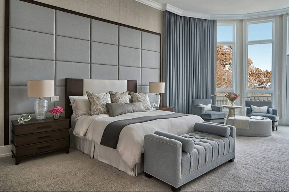 Transitional master bedroom with an oversized headboard that complements the gorgeous bench, upholstered armchairs and window curtains.