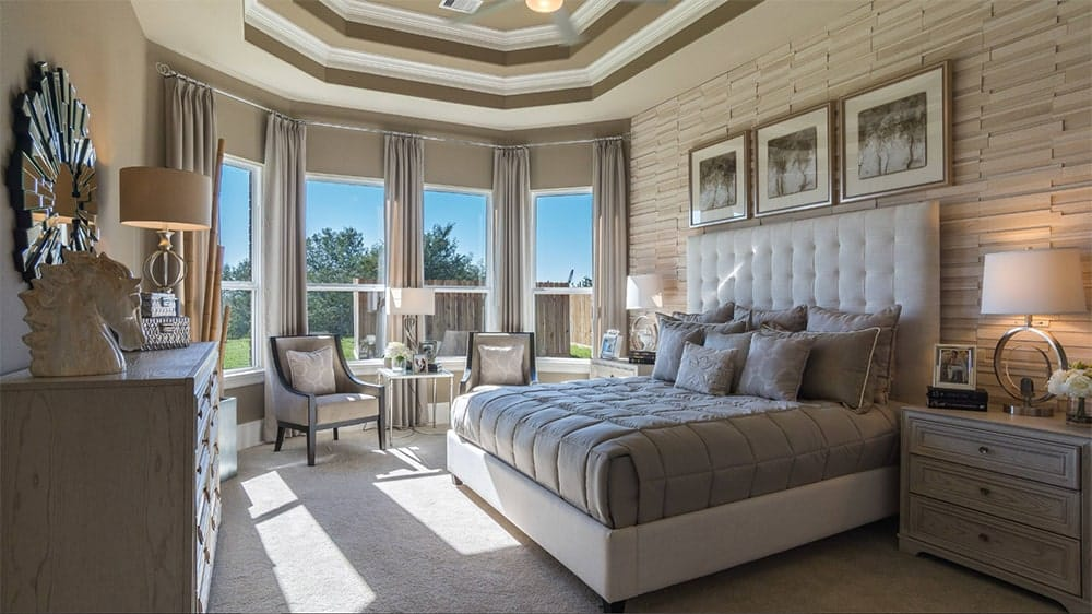 Cozy master bedroom features a tiled accent wall, multi-colored tray ceiling and carpet flooring along with a tufted bed and upholstered chairs.