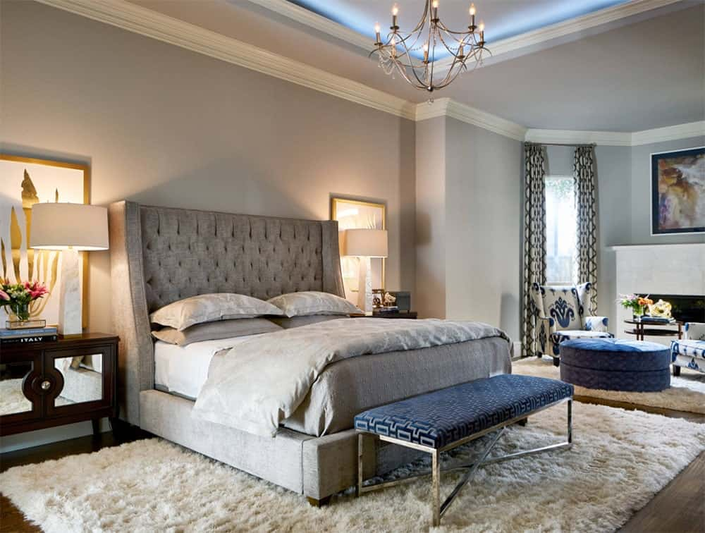 Gray and blue master bedroom with touches of gold features a tufted bed with velvet bench on its edge and sits over a cream shaggy rug.