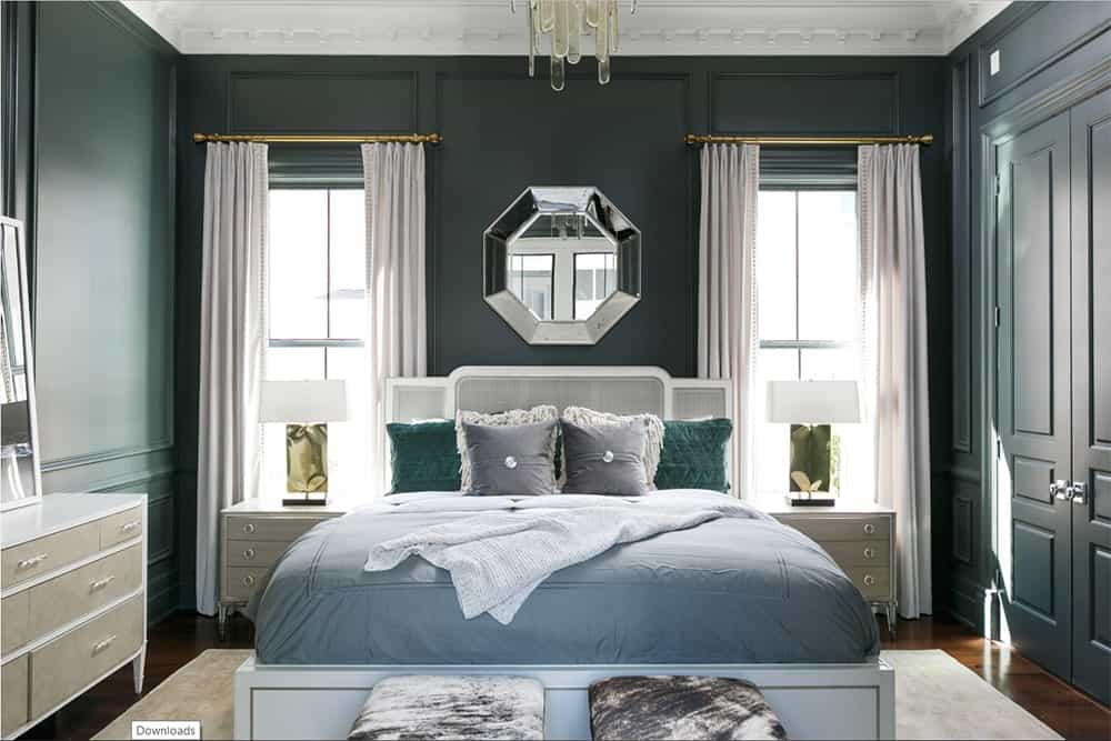 Beautiful dark green wainscoted walls give life to the symmetrical master bedroom. A silver octagon mirror mounted between windows creates an enticing focal point.