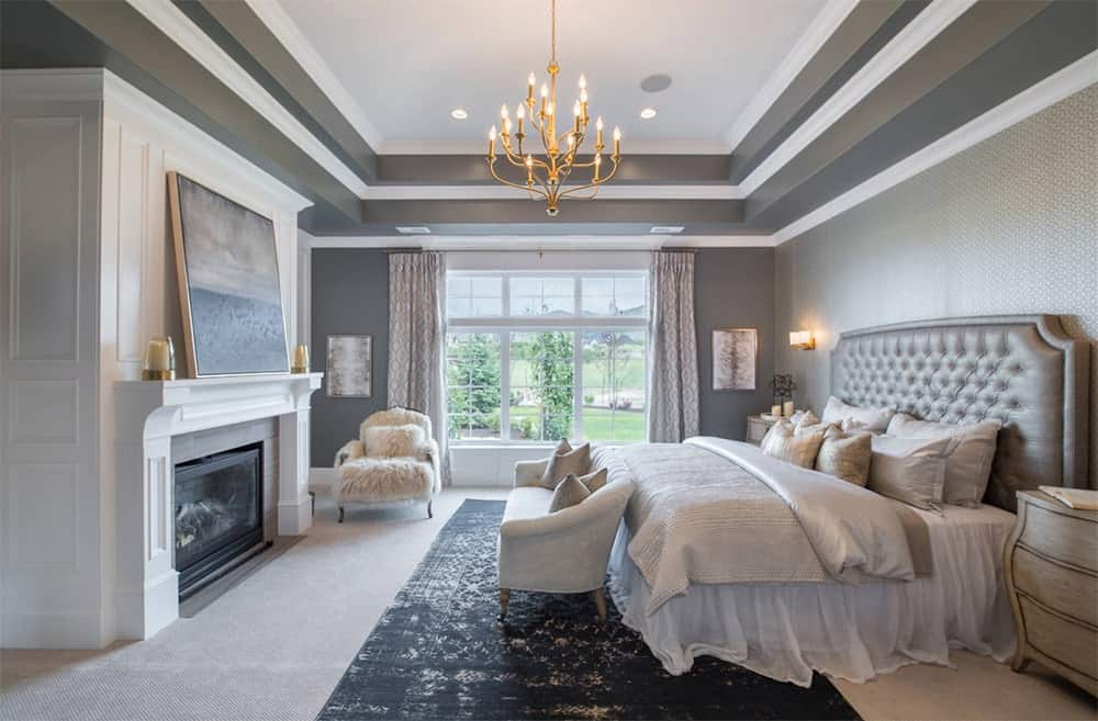 An elegant master bedroom features a leather tufted bed with sofa on its edge, highlighted by a black rug over a carpet flooring. It faces the fireplace paired with a white faux fur chair.