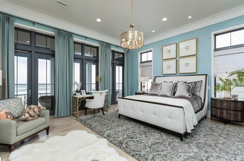 Light blue master bedroom with a beautiful white bed highlighted by gray velvet pillows and sits on a vintage rug over a hardwood flooring.