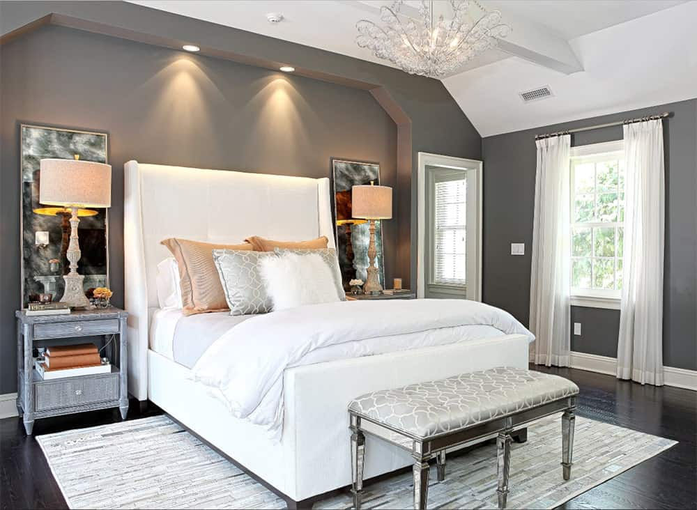 Luxurious master bedroom features gray walls and nightstands with lamps along with a crystal chandelier that hung over the white bed with a gray patterned bench on its end.