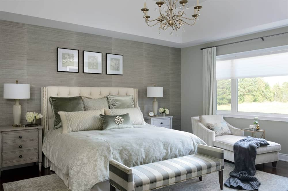 Sophisticated master bedroom accented with a striped-end bench and textured wall that matches the nightstands. It has a gold chandelier and a gray chaise lounge with throw blanket under the white framed window.