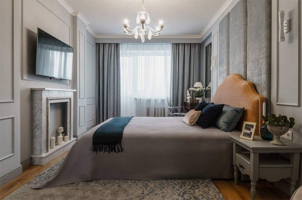 Gray transitional master bedroom with hardwood flooring, wainscoted walls and an oversized vertical tufted headboard illuminated by a fancy chandelier.
