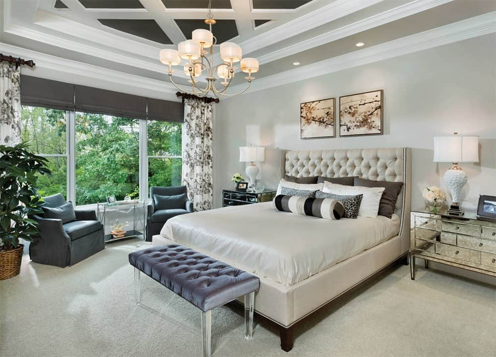 Luxurious master bedroom with a lovely chandelier that hung from a black coffered ceiling over a beige bed with gray velvet bench at its end. It also features a mirrored glass nightstands with white table lamps that add sophistication in the room.