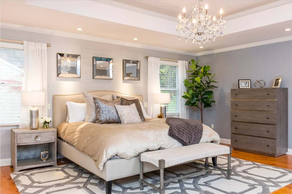 Magnificent master bedroom features a beige upholstered bed that sits on a geometric patterned rug and illuminated by a crystal candle chandelier. A fiddle leaf fig plant on the corner adds a fresh vibe in the room.