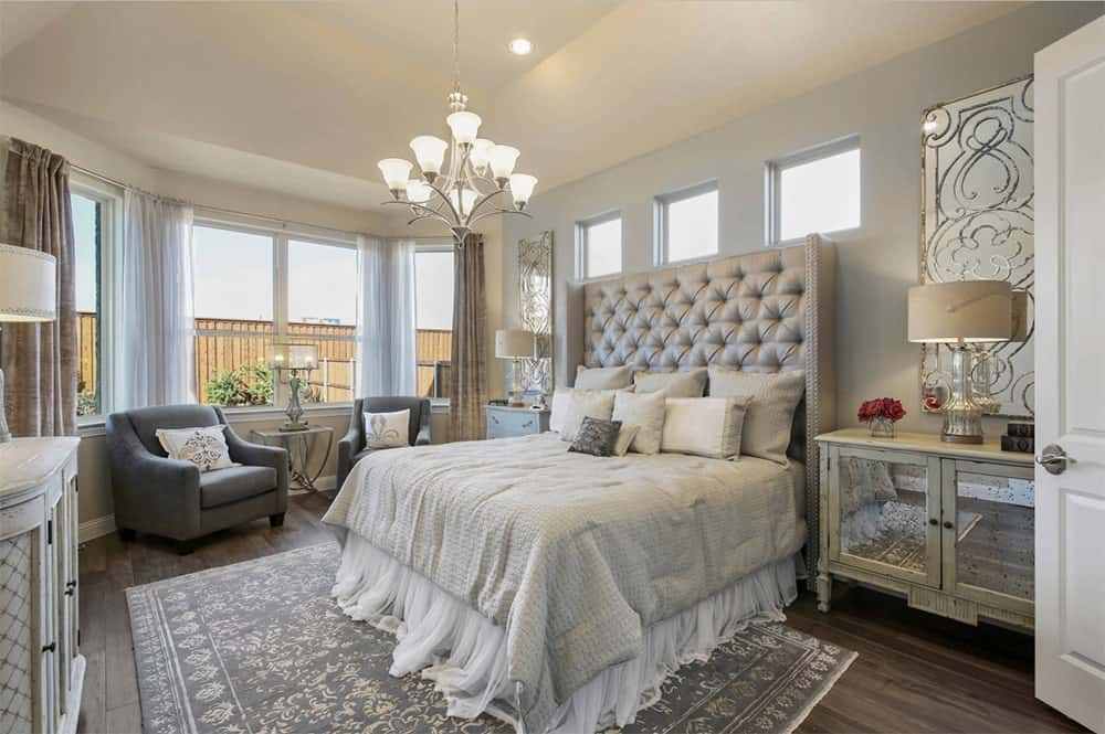 Warm transitional master bedroom features a gray tufted bed that sits on a vintage rug over hardwood floor and complemented by dark gray armchairs.
