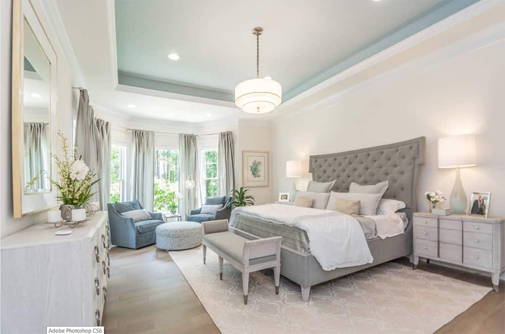 A fancy drum chandelier hung from a tray ceiling over a gray tufted bed on this transitional master bedroom. It features a patterned rug that sits on a hardwood flooring and nightstands that matches the cabinet.