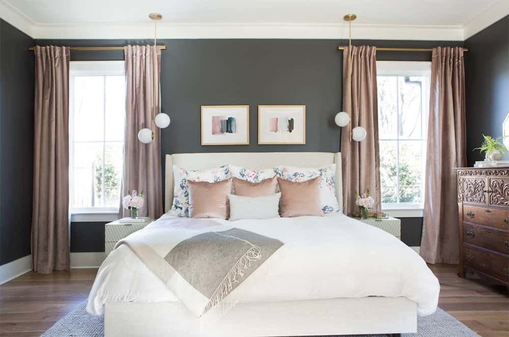 Charcoal and blush master bedroom with a white upholstered bed decorated by a pair of abstract wall frames and globe pendant lights.