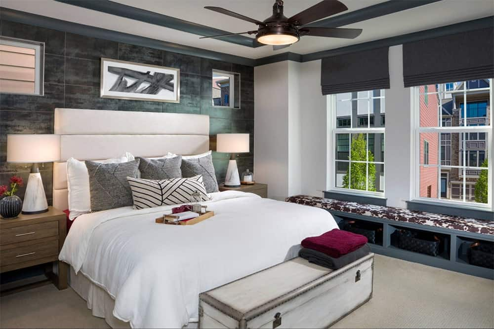 Transitional master bedroom features a window seat nook with built-in shelves, a black ceiling fan and a white bed with light wood storage chest bench on its end over a carpet flooring.