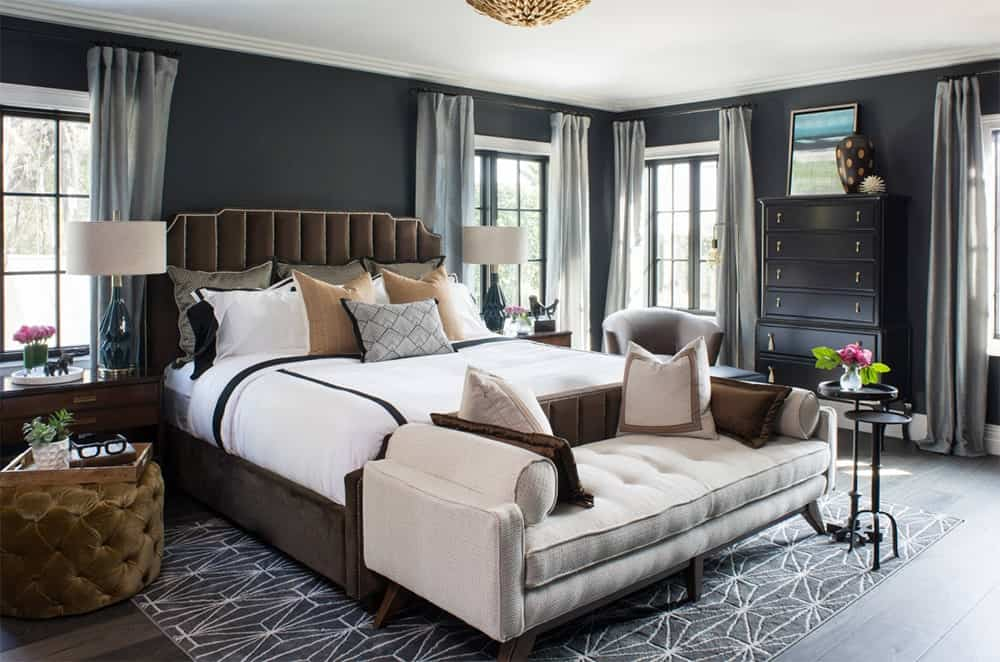 Elegant black master bedroom features a brown bed with vertical tufted headboard and a beige upholstered bench over a black patterned rug.