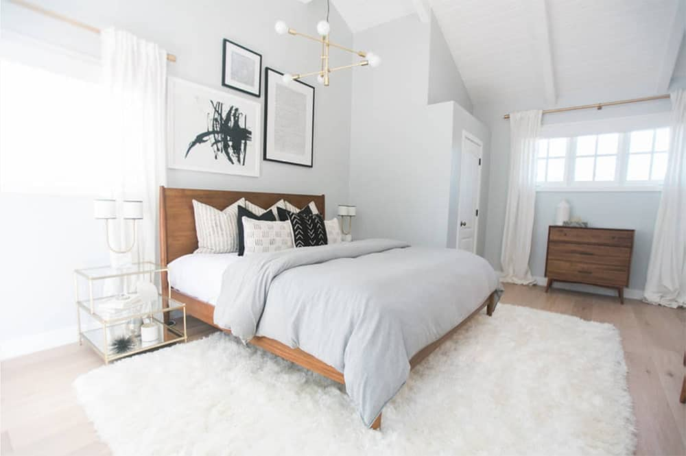 Fresh white master bedroom with a wooden bed frame that sits on a white shaggy rug along with glass nightstands. It is decorated by a modern industrial chandelier and gallery wall frames.