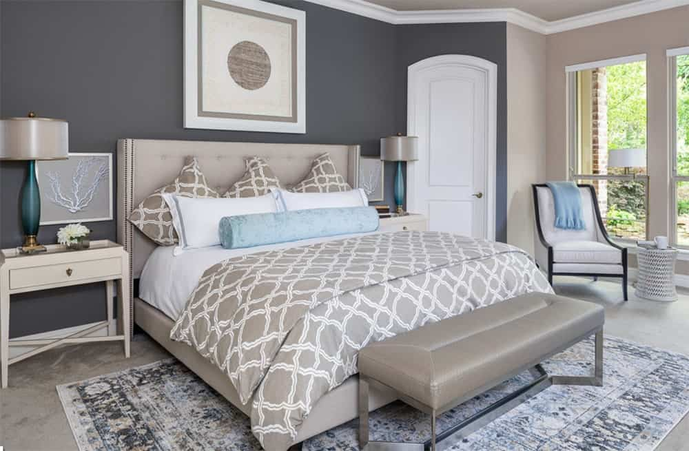 Gray and taupe master bedroom with blue accents from the table lamps, pillow and throw blanket. It features a tufted bed that matches the bench on its end and glass windows overlooking the outside scenery.