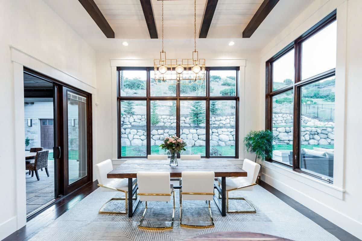 Bright dining room surrounded by large windows and sliding doors that open to a covered porch. It is topped with a beamed ceiling graced with a brass chandelier that matches the modern chairs.