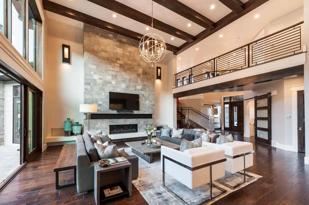 Spacious living room with contemporary seats, natural wood tables, a large stone fireplace, and a spherical chandelier that hangs from the beamed ceiling.