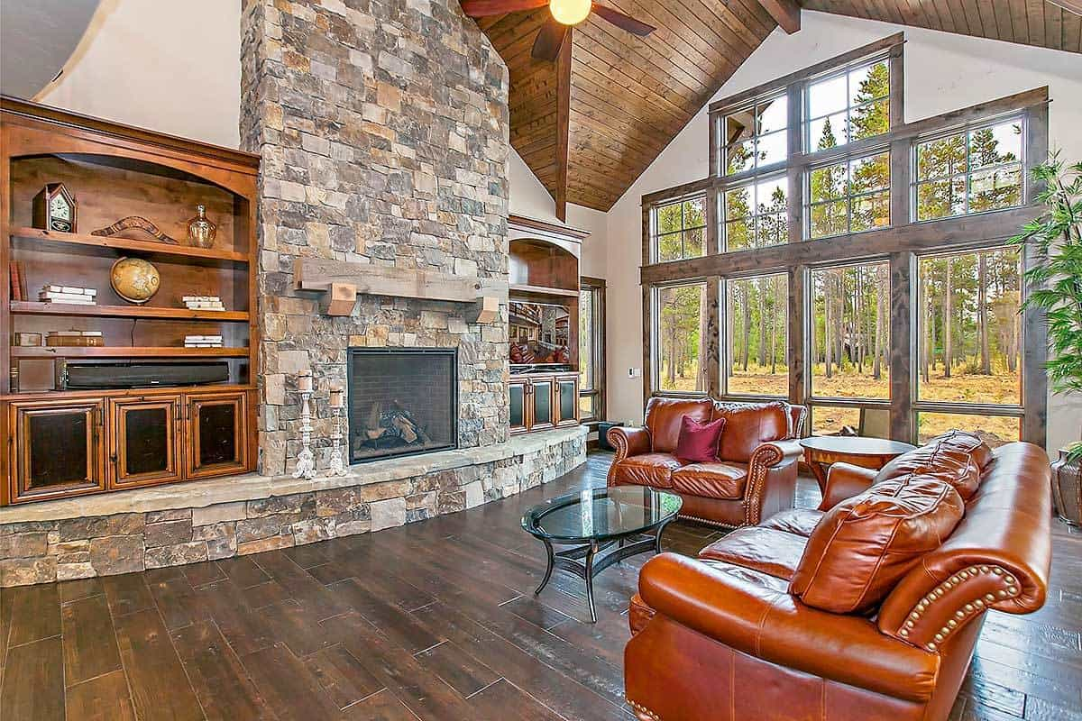 This is a spacious and bright living room with a tall dark wooden arched ceiling that matches the dark hardwood flooring. This makes the brown leather sofa set and glass-top coffee table stand out across from the large stone structure that houses the fireplace.