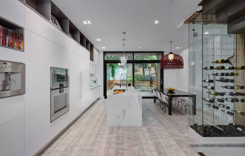 An extravagant white kitchen with casual dining area and wine cellar in a glass enclosure. It has a white marble breakfast island and glass doors leading to the back patio.