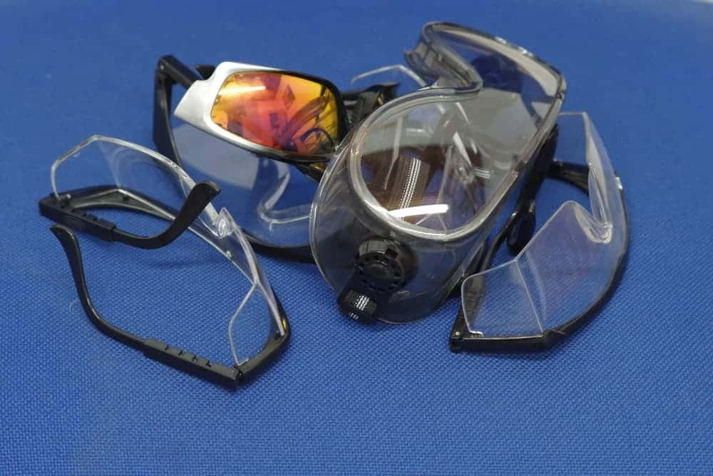 Various types of safety goggles on a blue background.