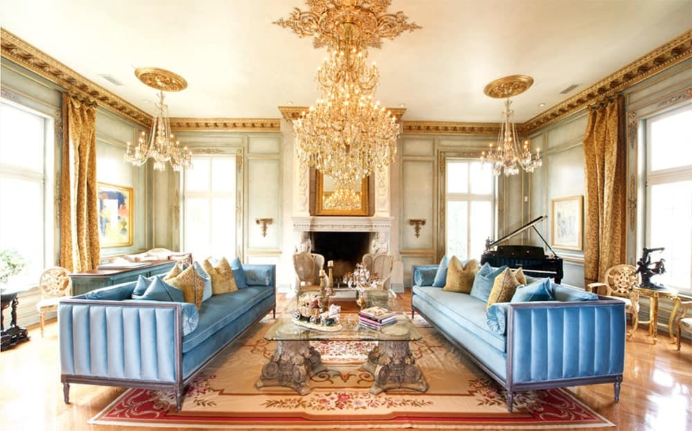 A pair of matching blue velvet sofas with a glass top coffee table on the center stands out in this symmetrical living room. It includes gold crystal chandeliers that add elegance to the area.