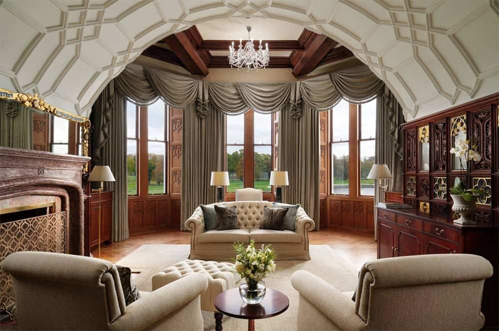 An arched coffered ceiling highlights this living room along with glazed windows fitted with scallop curtains.