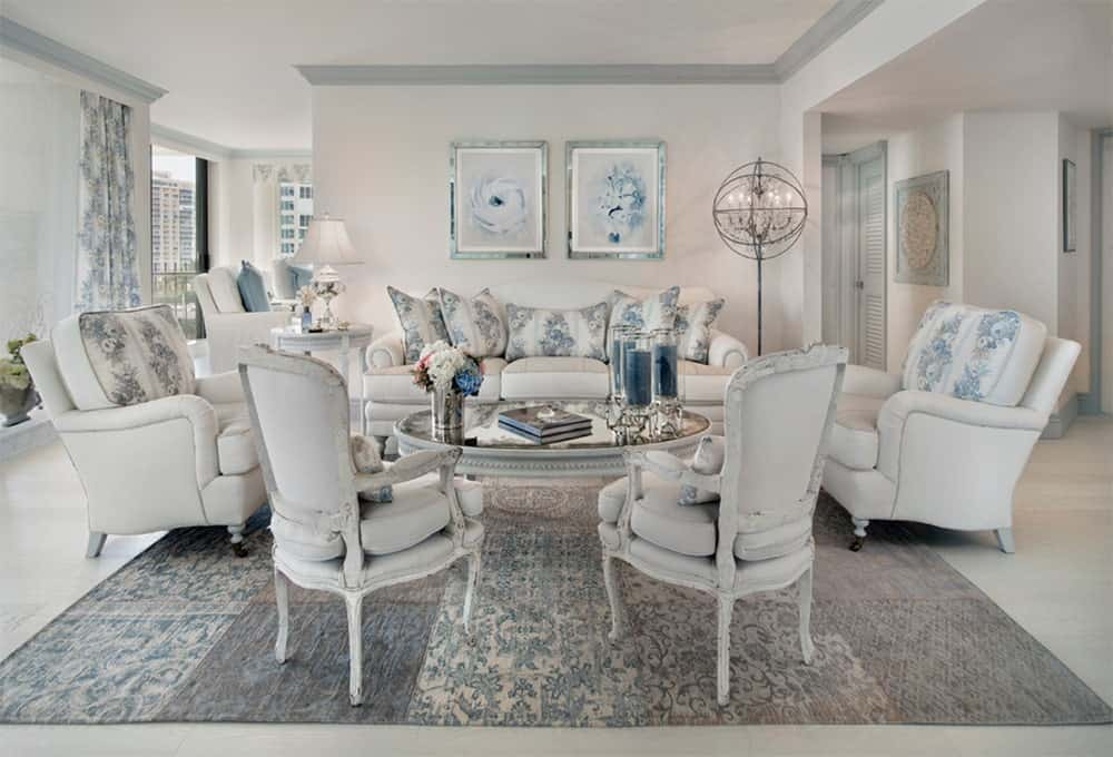 Gorgeous living room boasts stunning white pieces accented with blue floral pattern. It is lighted by a unique vintage floor lamp which is another highlight of the room.