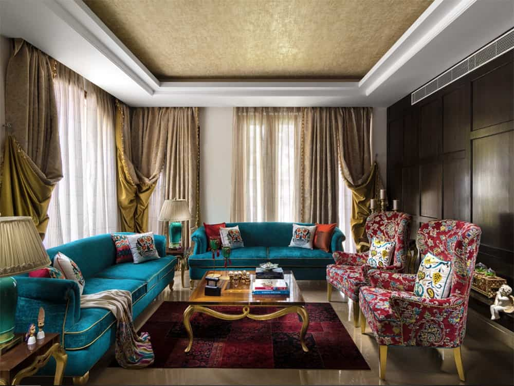 Sophisticated living room showcases a pair of vibrant blue green sofas contrasted by another pair of red floral wingback chairs. It has beige marble flooring that complements with the tray ceiling.