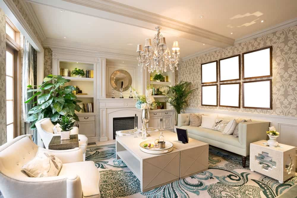 Victorian living room features a classy swirl pattern wallpaper above white wainscoting. It is lighted by a fancy crystal chandelier that hung over the beige coffee table.