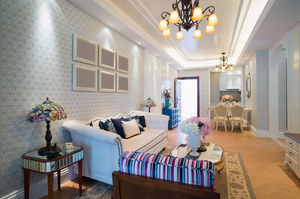 Vintage chandeliers that hung from a tray ceiling illuminates this white living room covered in charming blue wallpaper. It is designed with blank gallery frames mounted above the white tufted couch.