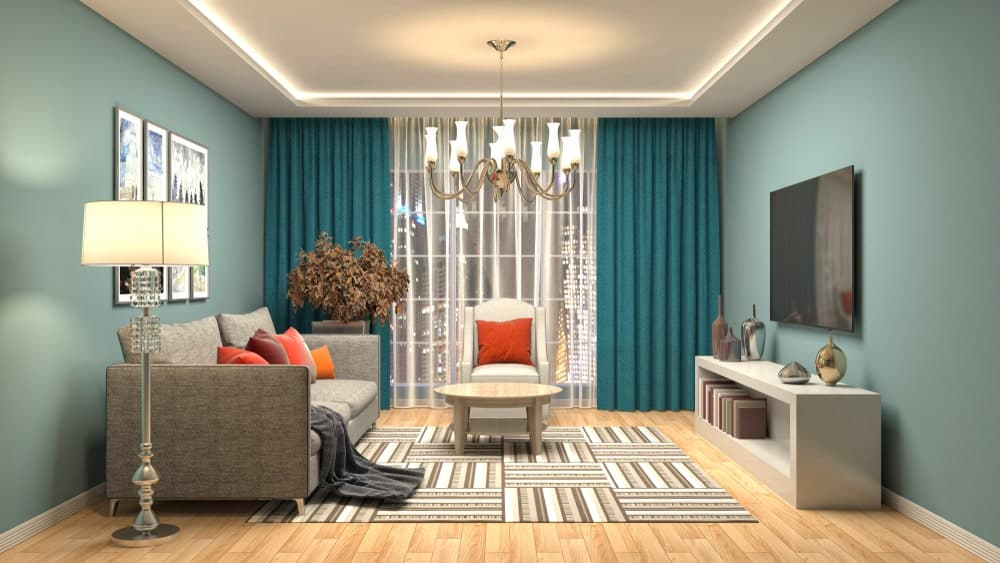 Enchanting blue living room features a floor to ceiling window covered with sheer and teal curtains. It is illuminated by an oversized chandelier and floor lamp next to the gray sofa accented with multi-colored pillows and a gray throw blanket.