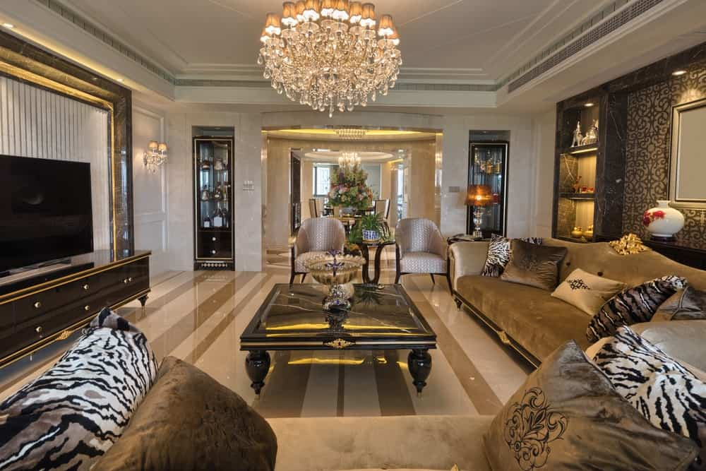 Luxurious living room showcases velvet taupe sofas and armchairs surrounding a black center table. It is designed with display cabinets and shelves filled with home decors and lovely vases.