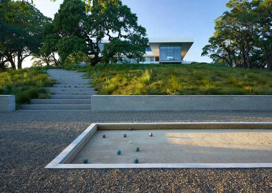 A bocce ball court surrounded by a gravel courtyard with concrete stairs leading to the glazed house. Large, beautiful trees covering the house on a slope hill add privacy to the yard.