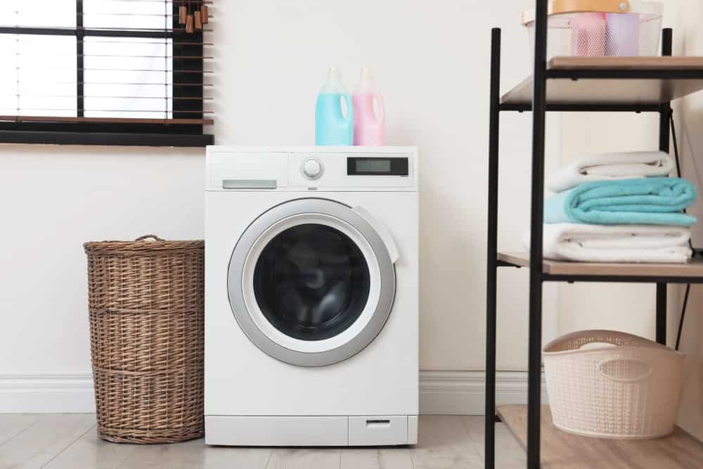 A small washing machine beside a laundry basket in the laundry room.
