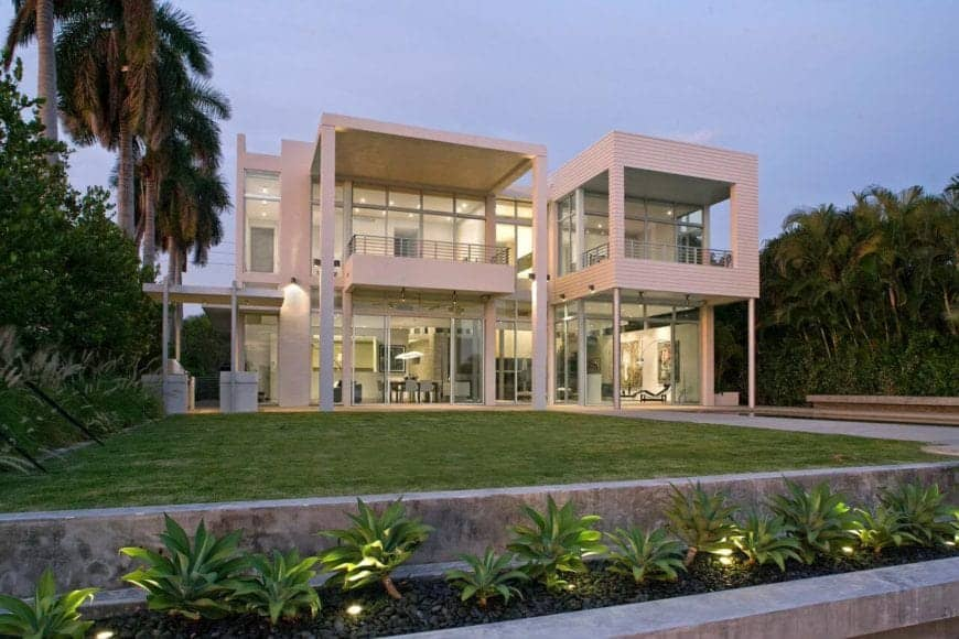 Modern, beautiful house with a lush green lawn surrounded by tropical trees along the concrete pavement.