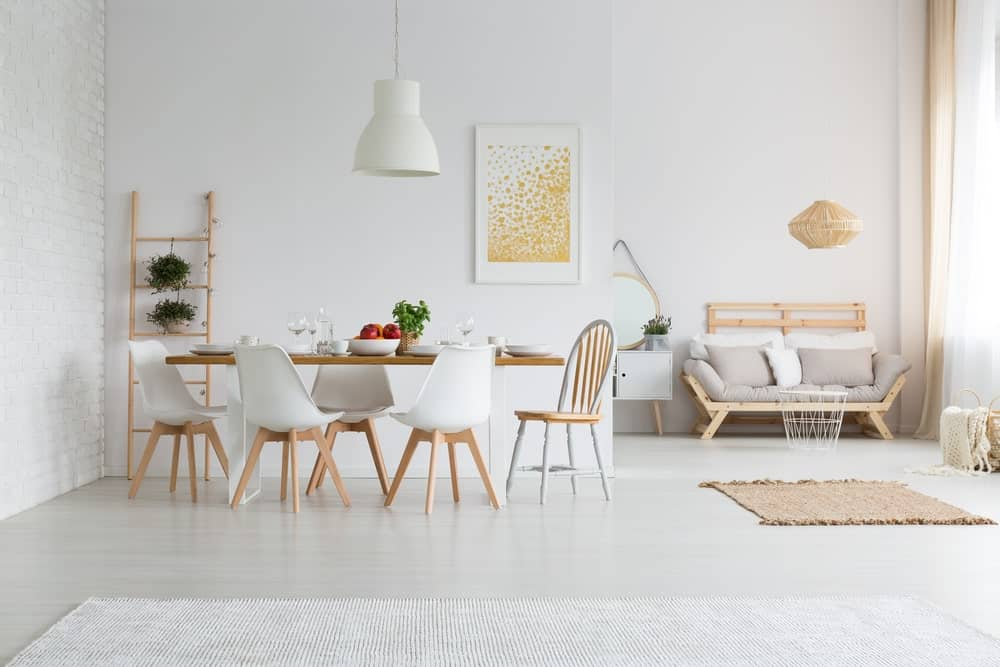 White dining room featuring a large pendant light set just above the dining table set.