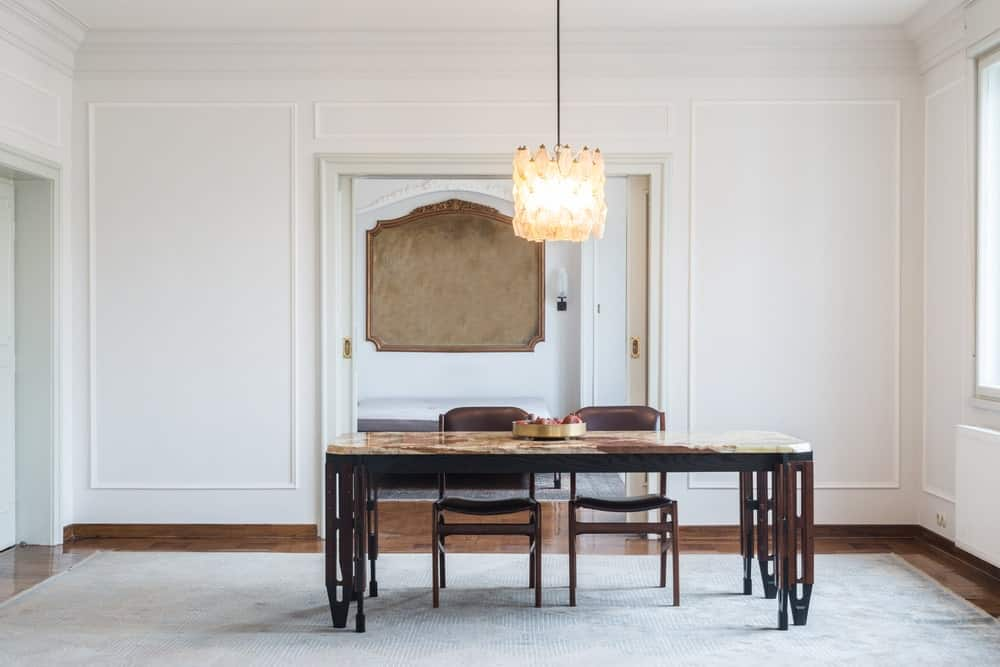 White dining room featuring a large rug covering the smooth brown flooring. The table looks absolutely elegant, perfect together with the ceiling lighting.
