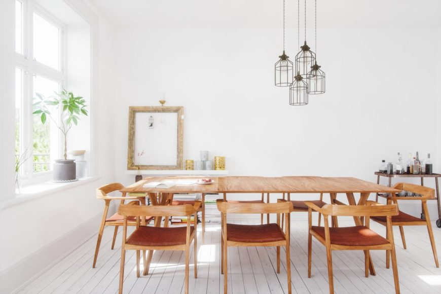 Large dining area featuring white walls and white hardwood floors, along with a wooden rectangular dining table set.