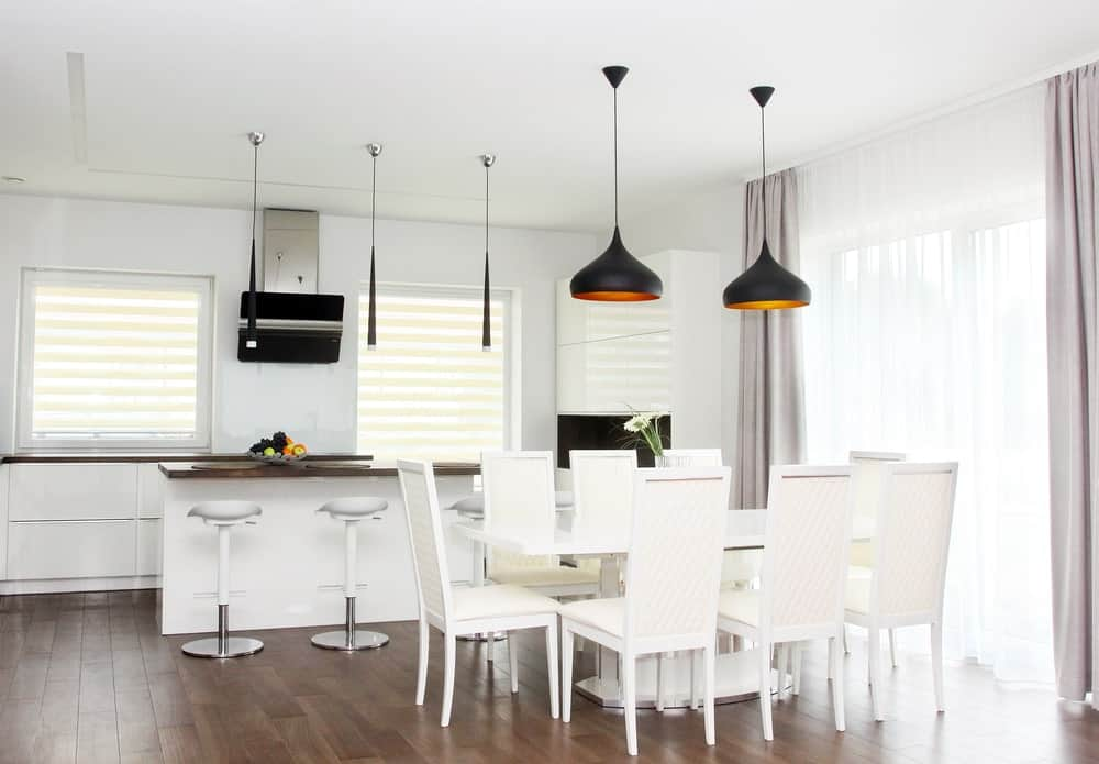 A dine-in kitchen with a breakfast bar and white dining table set lighted by stylish black pendant lights hanging from the home's tall ceiling.