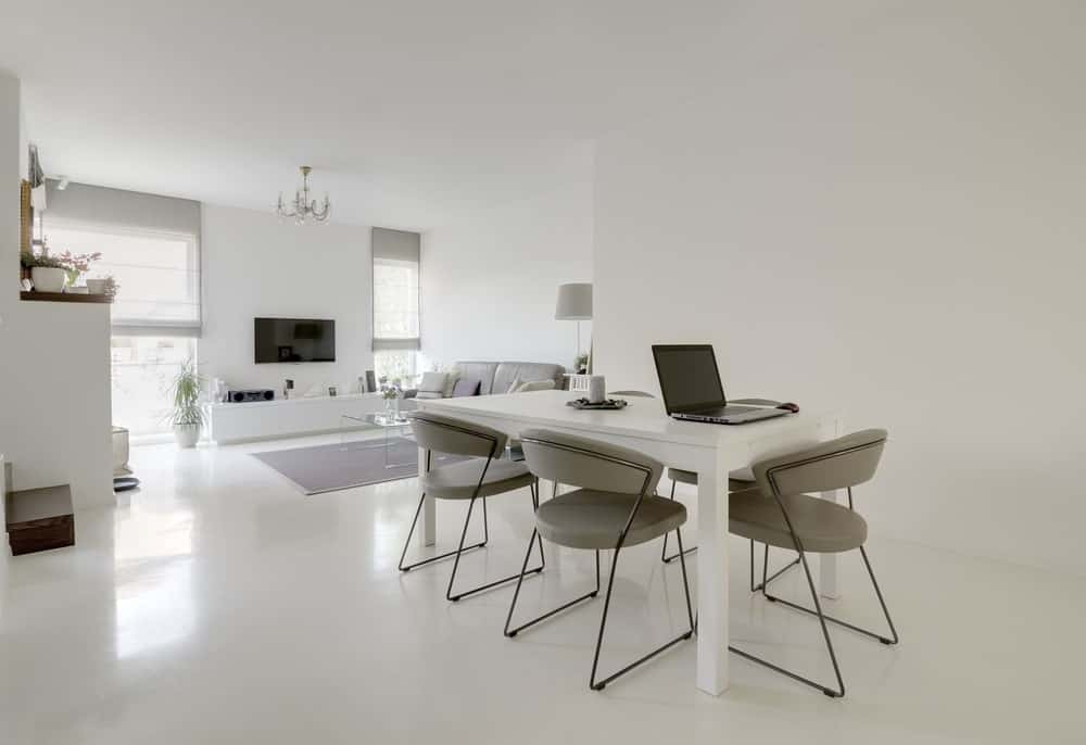A great room featuring a formal living space and a modern dining table set. The home has white walls and ceiling.