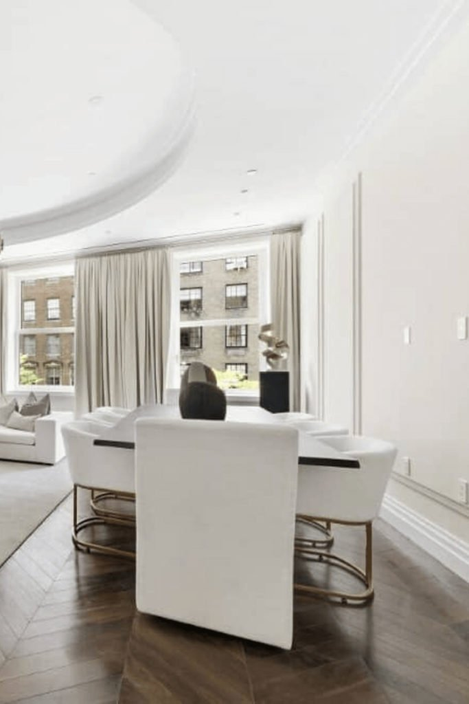 This white dining room showcases pristine walls and ceiling contrasted by chevron wood flooring. The area is furnished with a rectangular dining table and white modern chairs.