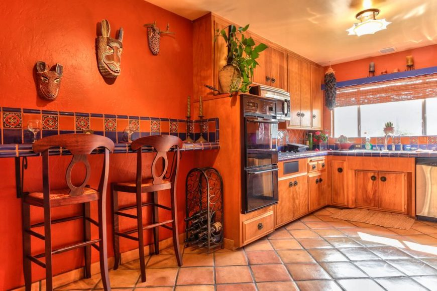 Red kitchen accented with blue tiles countertops and backsplash and designed with faux animal head decors. There's a floating breakfast bar paired with wooden counter stools.