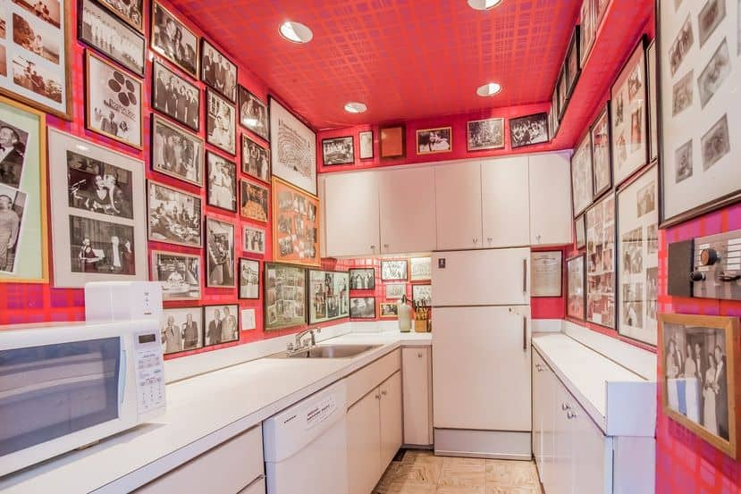 A bunch of picture frames mounted on the pink wall along with white cabinetry surrounded this U-shaped kitchen.