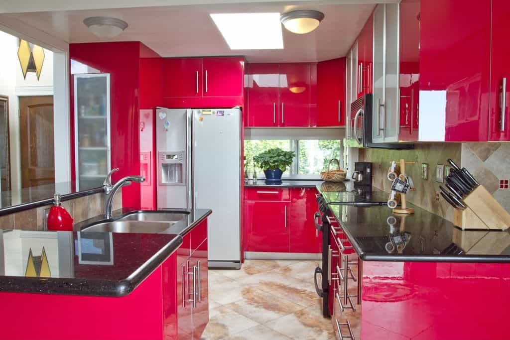 Pink kitchen with glossy cabinetry and black marble countertop illuminated by dome ceiling light fixture and a skylight.